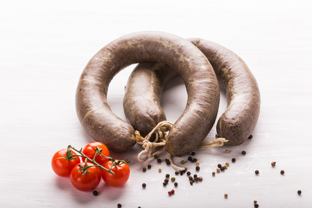 Food, horse meat and delicious concept - sliced sausage with tomato and pepper