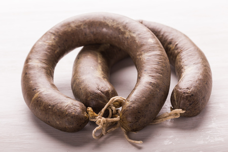 Food, meat and delicious concept - sliced horse meat sausage with cumin Standard-Bild