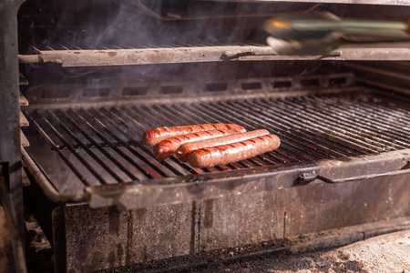 food, delicious and craft concept - grilled sausage on the flaming grill Stock Photo