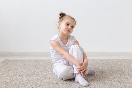 Children and kids concept - Little child girl dressed in white shirt sitting on the floor with thoughtful face