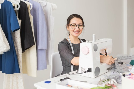 People, tailor and fashion concept - High angle view portrait of smiling fashion designer in glasses sitting at a table