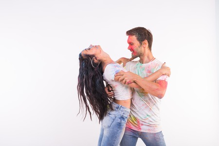 Holiday, social dance, holi and people concept - Happy couple having fun covered in paint and dancing bachata or kizomba on white background with copy space