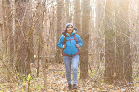 adventure, travel, tourism, hike and people concept - smiling tourist woman walking with backpacks over autumn natural background Stok Fotoğraf