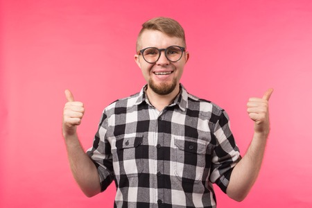 Youth, gesture and good concept - young man looks like a nerd show us thumbs up over the pink background Banque d'images