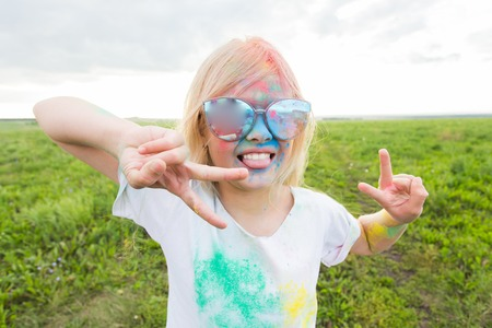 Children, festival of holi and holidays concept - happy little girl covered with color powder smiling over nature background Stock Photo