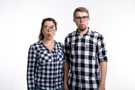 Nerds, geek, bespectacled and funny people concept - funny couple in glasses are hugging on white background