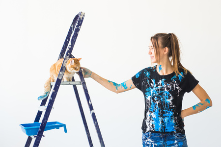 Young woman painter, designer and worker paints the wall. The cat sits next on the ladder and looks at the work. Stockfoto