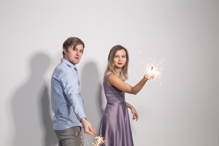 Fun, love and holiday concept - man and woman fooling around with sparklers