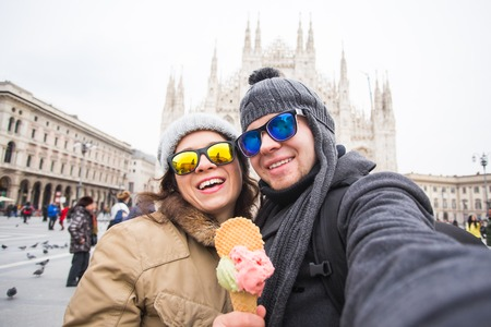 Travel in winter concept - Young and happy tourist making selfie photo in front of the famous Duomo cathedral in Milan. Happy vacations in Milan