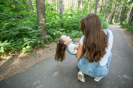Family, nature and people concept - Mother and daughter spend time together on a walk in the forest