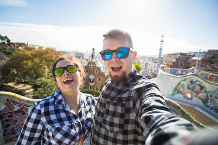 Funny young couple looking at camera taking photo with smart phone smiling in Park Guell, Barcelona, Spain. Imagens