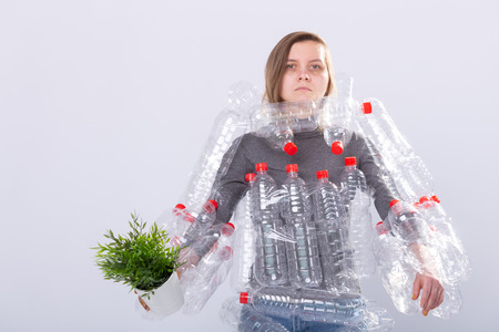 Environmental Protection, people and recyclable plastic concept - exhausted woman concerned with environment disaster with dress as plastic bottles holding green plant on white background