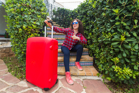 Travel, vacations and holidays concept - happy traveller woman sitting on stairs in sunny glasses with red suitcase and showing thumbs up
