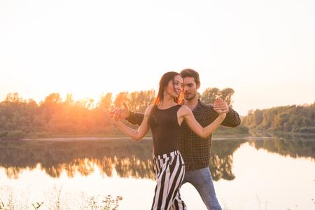 Kizomba, bachata, zouk and latin social dance concept - Man and woman dancing over nature background