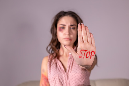 Domestic violence, protesting and people concept - brunette woman expressing denial with STOP on her hand on grey room