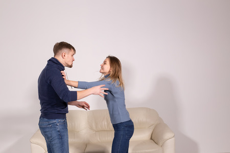 people, violence and abuse concept - young aggressive man hitting his girlfriend in her arm 스톡 콘텐츠