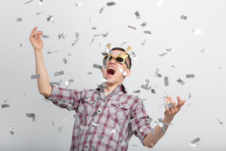 People, holidays and party concept - funny guy in glasses dancing in confetti on white background Imagens