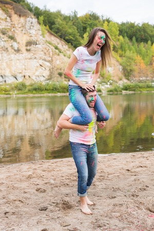 Festival holi, summer tourism and nature concept - young attractive girl sitting piggyback on her boyfriend on nature