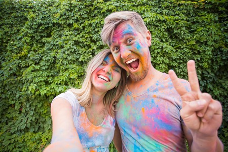 Festival holi, people concept - young couple taking selfie in colourful dirty clothes 스톡 콘텐츠