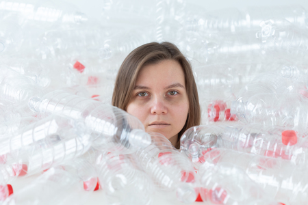 Dehydrated sick woman is lying in a pile of plastic bottles. Environmental pollution problem. Stop nature garbage environment protection concept Stock Photo