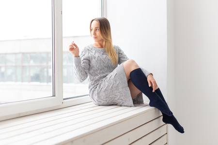 People and fashion concept - Gorgeous romantic woman in wool dress sitting on the window sill