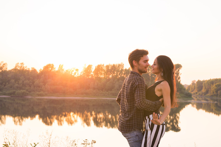 Romantic, social dance and people concept - young couple dancing bachata on the background of sunset