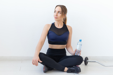 People, sport and fitness concept - young woman sitting with bottle of water on gym mat