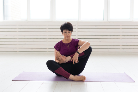 People, yoga, sport and healthcare concept - Attractive middle-aged woman stretching and sitting in yoga lotus position Stock Photo