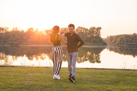 Romantic, social dance, people concept - young couple dancing bachata near the lake in sunny day
