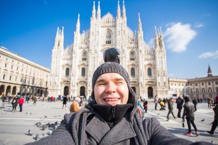 Italy, excursion and travel concept - funny guy taking selfie with pigeons in front of cathedral Duomo in Milan