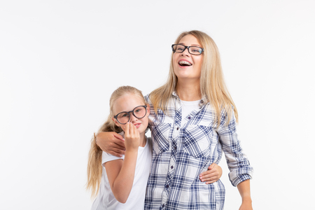 Portrait of mother and daughter with eyeglasses on white background