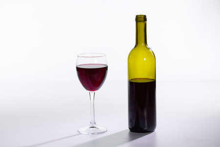 Bottle and glass with red wine on white background 写真素材