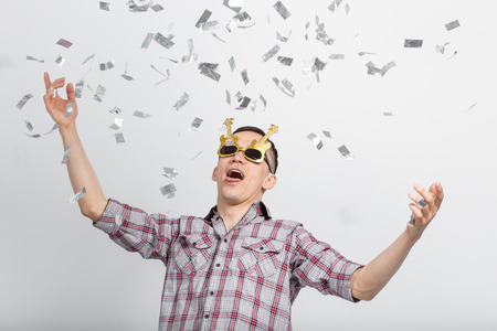 People, holidays and party concept - funny guy in glasses dancing in confetti on white background Banco de Imagens
