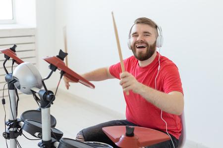 Concepto de música, personas y pasatiempos: hombre baterista tocando el tambor y parece muy emocional