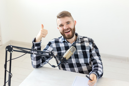 Radio host, streamer and blogger concept - Portrait of smiling man gesturing thumbs up, hosting a show at radio station or his blog Banco de Imagens