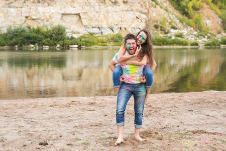 Festival holi, summer tourism and nature concept - young attractive woman sitting piggyback on her boyfriend on nature Stockfoto