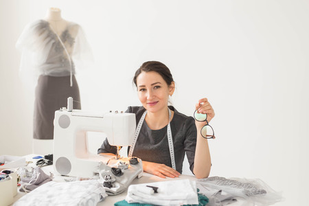 Dressmaker, tailor and creative concept - Portrait of fashion designer with sewing machine over white background Banque d'images