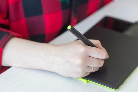 Concept d'entreprise, de designer et d'animateur - gros plan sur la main du graphiste dessinant sur la tablette