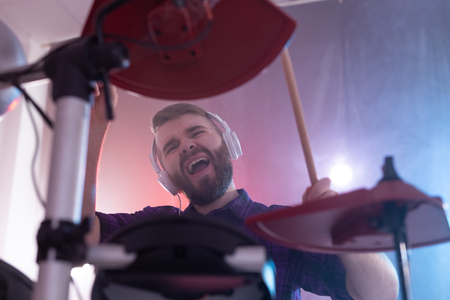 Drums, music and people concept - emotional man playing on elecronic drums, its his hobby