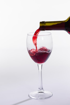 Red wine pouring into glass from bottle on white background