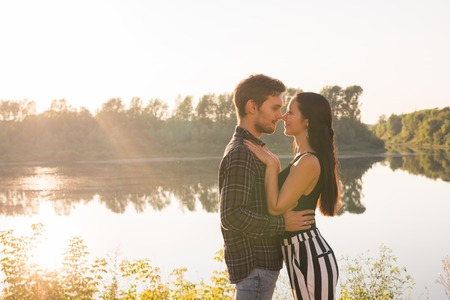 People, love and nature concept - Portrait of young beautiful couple embracing each other while standing over nature background