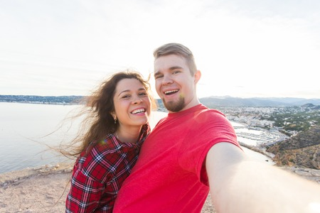 Travel, vacation and holiday concept - Beautiful couple having fun, taking selfie, crazy emotional faces and laughing. Stock Photo