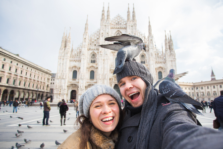 Travel, Italy and funny couple concept - Happy tourists taking a self portrait with pigeons in front of Duomo cathedral, Milan Фото со стока