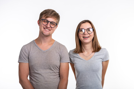 People and education concept - Two young funny student with thoughtful faces over white background