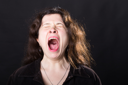 Negative emotions concept - Scared screaming young woman standing over black background.