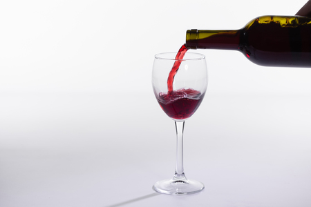 Red wine pouring into glass from bottle on white background.