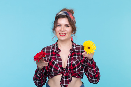 Gerberas, pin-up and fun concept - cheerful young woman with flowers in retro style on blue background