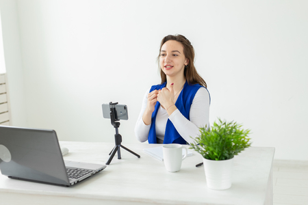 Blogging, work and vlog concept - young woman blogger is speaking to the camera