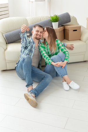 Charming young woman kisses her husband holding in hands the keys to their new apartment while sitting in her new living room