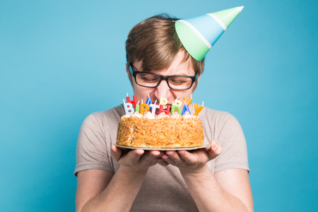 Funny male in paper congratulatory hat trying to bite off a cake with a happy birthday candles stand on a blue background.